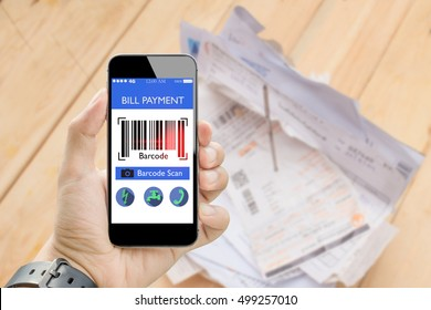 man holding smart phone online bill payment with bar code scan with blurred utilities bill on wooden table in background,fake barcode