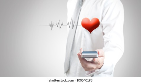 Man holding smart phone showing red heart and pulse