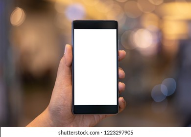 Man holding smartphone with blank screen at shopping mall. Take your screen to put on advertising.
