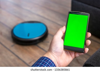 Man holding a smartphone and controling a robot vacuum cleaner through an app.