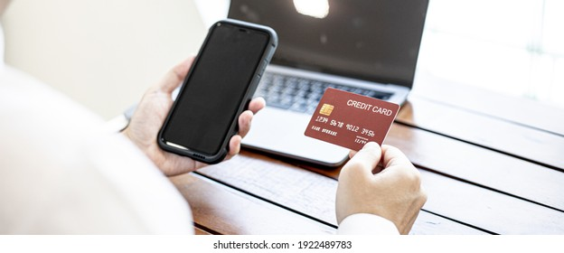 A man holding a smartphone and credit card. He fills his credit card information with a smartphone to pay for the goods ordered on the website, credit cards can pay for goods and services online.