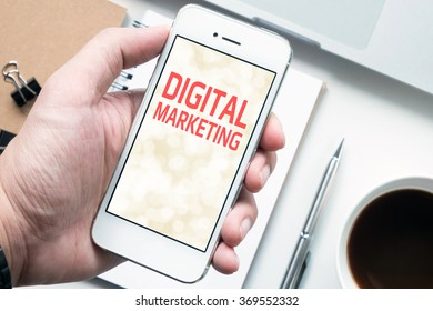 "A man is holding a smartphone with ""DIGITAL MARKETING"" texts on a screen. Mobile marketing concept. Top view."