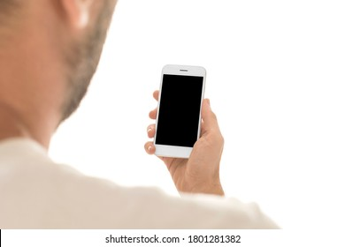 Man holding a smartphone with empty black screen. Mobile phone in a vertical position in hands and isolated on white background. Studio shot. Third person view. Camera shot from over shoulder.