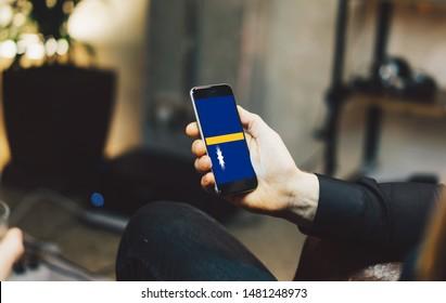 Man holding Smartphone with Flag of Nauru. Nauru Flag on Mobile Screen.