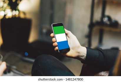 Man holding Smartphone with Flag of Sierra Leone. Sierra Leone Flag on Mobile Screen.