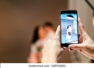 a man holding smartphone in hand, taking photography pre-wedding of couple in studio for sent a message, upload or share in social media. Wedding and phone concept with copy space, selective focus.