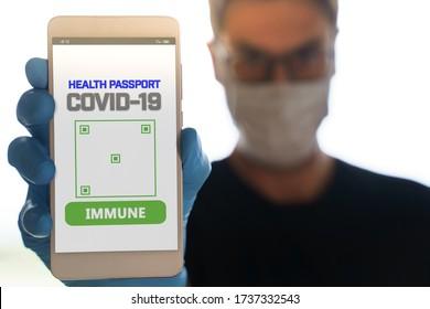 Mann mit einem Smartphone mit Immun-digitalen Pass für covid-19. Geeignet für die Anwendung des Immunpasses am Telefon zur Überwachung der Bewegungen der Bevölkerung am Ende des Absturzes