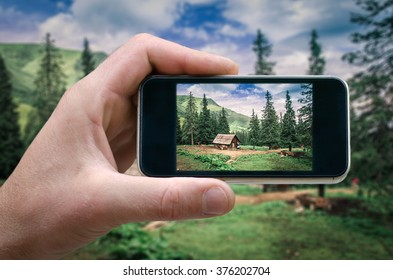 man holding a smartphone and photographed mountain landscape, photographed on a smartphone, selfie phone