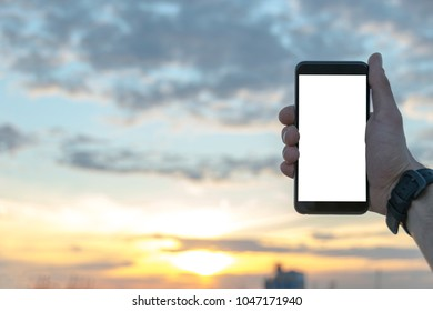 Man Holding smartphone at the sunset with isolated white screen. Empty space for text. Isolated screen for mock up. Workplace with copy space.