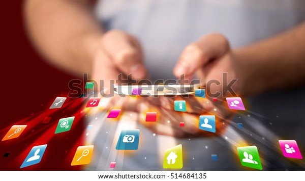 Man holding smartphone with technology application icons comming out
