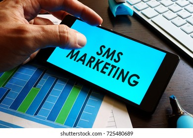 Man holding smartphone with words sms marketing.