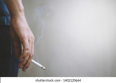 man holding smoking a cigarette in hand. Cigarette smoke spread. dark background