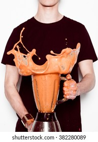 Man holding splashing blender