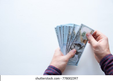 man holding a stack of US dollars banknotes