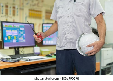A man holding a staff safety helmet with radio communication in production control room. There is a computer in the control of machinery at feed mills. communication and Safety at work