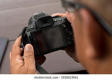 Man holding and starring at the blank screen camera