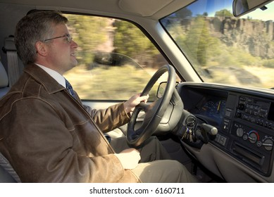 Man holding steering wheel driving a truck wearing leather jacket