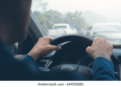 Man holding steering wheel, driving a car in the rain, careful driving in rainy day, left hand drive, close up