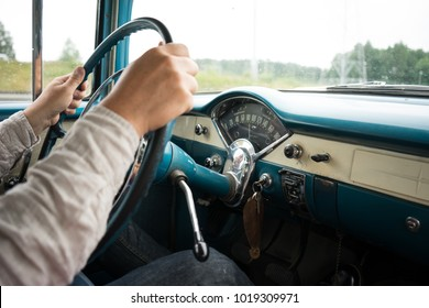 Man holding the steering wheel of an old car with the dashboard in view