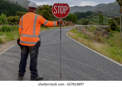 Man holding STOP signal on the rural road