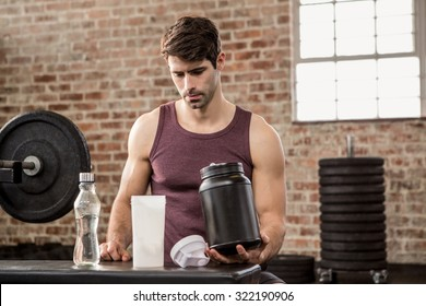 Man holding supplement tin at the gym