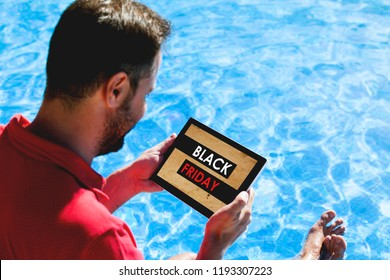 Man holding a tablet with Black Friday sales in the screen, while sitting on the poolside.