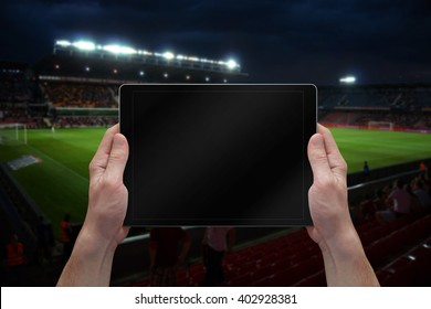 Man holding tablet with blank screen on soccer game. Stadium in background.