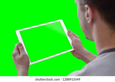 Man holding tablet in horizontal position. View over the shoulder. Isolated screen for mockup, and background in green for video editors.