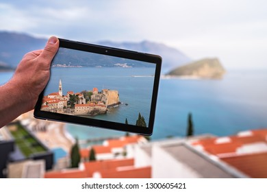 Man holding tablet with the image of Budva while standing on the balcony of his apartment in Budva town, Montenegro