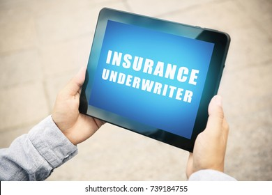 Man holding tablet with text INSURANCE UNDERWRITER on screen outdoors