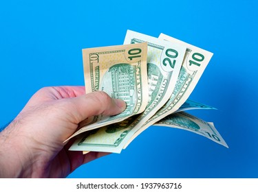 A man holding ten and twenty United States dollar bills in his hand with blue background.