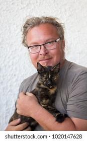 Man holding three-colored Cretan cat