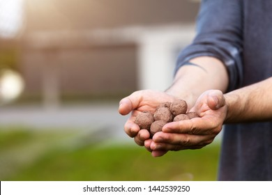 man is holding and throwing seed balls or seed bombs in front of a ugly grey building, concept guerilla gardening