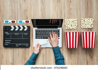 Man holding a ticket and watching a film streaming online with popcorn, 3D glasses and clapboard, movies and cinema concept