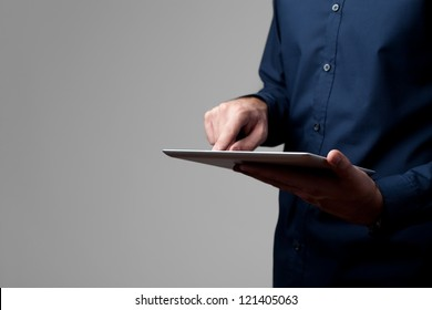 Man holding and touching digital tablet isolated on gray.