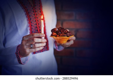 man holding traditional ramadan food at night