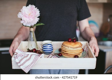 man holding a tray with breakfast of pancakes with cherry