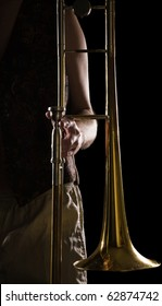 man holding a trombone; strong contrasting side-light; color version