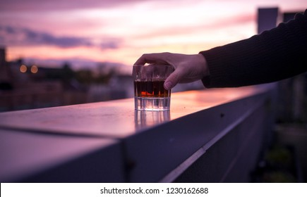 A man holding a tumbler of premium whkskey on a rooftop bar during a colorful sunset.