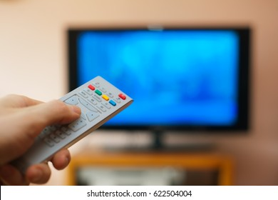 Man holding tv remote controller in from of tv screen.
