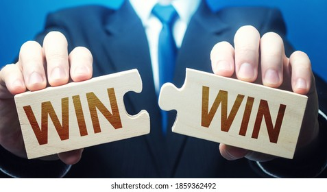 Man holding two puzzles with Win-Win words. A negotiation strategy makes all parties succeed. Mutual benefit and good contract terms. Compromise, perfect. Consent and satisfaction. Trade and diplomacy