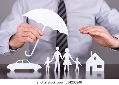 Man holding an umbrella protecting a family, a house and a car