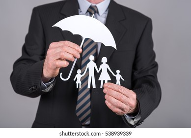 Man holding an umbrella protecting a family