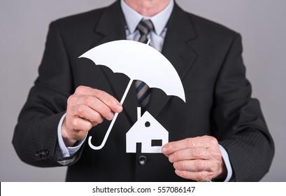 Man holding an umbrella protecting a family