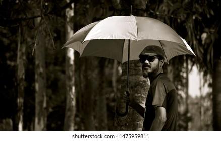 Man holding an umbrella standing around a place