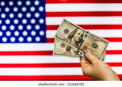 Man holding US Dollar bank note indicating market crash due to new US president with flag background