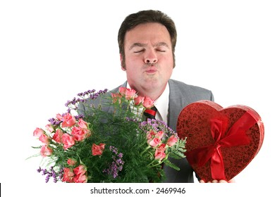 A man holding Valentines candy and flowers and puckering up for his thank you kiss.  Isolated on white.