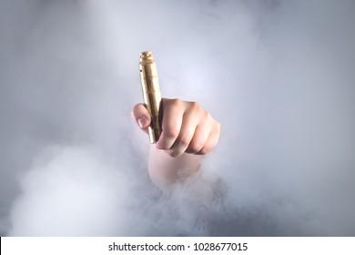 Man holding vaping device in smoke