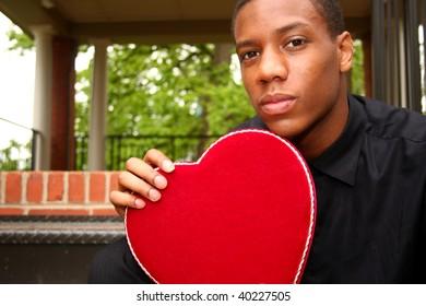 A man holding a velvet heart shaped box