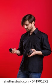 Man holding vintage camera and lens. Photographer lens changes. Hipster in black shirt and jeans.